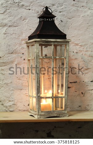 lamp with a candle on the shelf background stone wall - stock photo