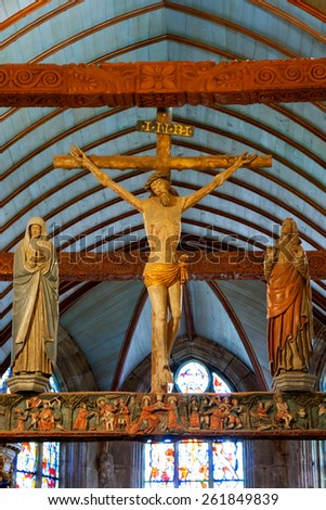 Lampaul-Guimiliau, FRANCE - JULY 20, 2014: Wooden crucifix of Jesus Christ in parish Notre Dame church. The Notre-Dame of Lampaul-Guimiliau was built in the sixteenth century. - stock photo