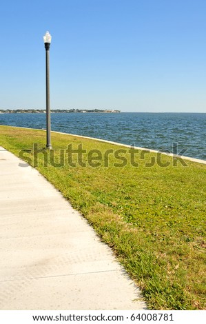 Lamppost, located in one of the many parks of St. Petersburg, overlooks the waters of Tampa Bay. Its light assists joggers, bicyclists and pedestrians walking on the adjacent sidewalk. - stock photo