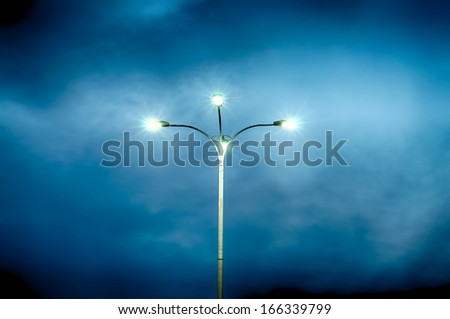 Lamppost with four lamps over background of a dramatic sky. HDR image. - stock photo