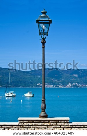 lamppost with light bulb on the waterfront - stock photo
