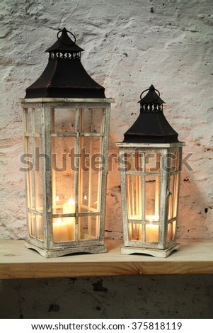 lamps with a candle on the shelf background stone wall - stock photo
