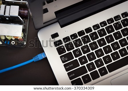 LAN cable is connecting internet to laptop with circuit board isolated on black background - stock photo