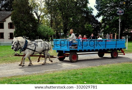 Lancaster, Pennsylvania - October 14, 2015:  Driver in high straw hat takes children for a wagon ride pulled by two white horses at the Landis Valley Village and Farm Museum