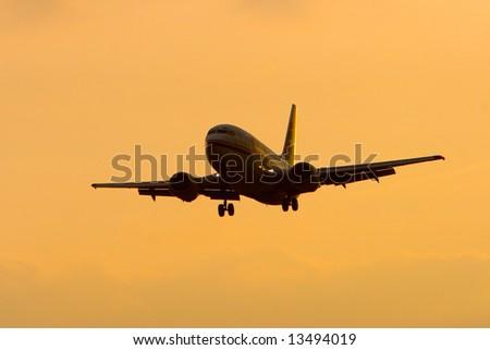 Land an large airplane during sunset - stock photo