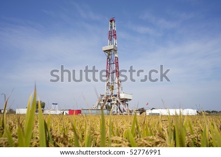 Land drilling rig surround by paddy field in China - stock photo