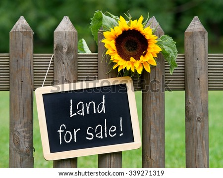 Land for sale - chalkboard with text and sunflower - stock photo
