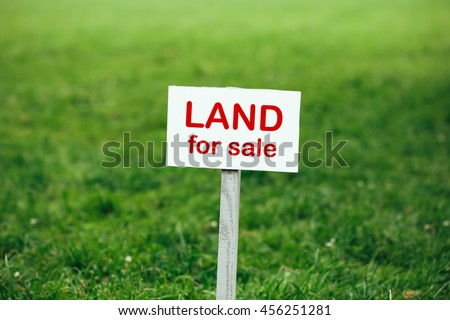 land for sale sign against trimmed lawn background - stock photo