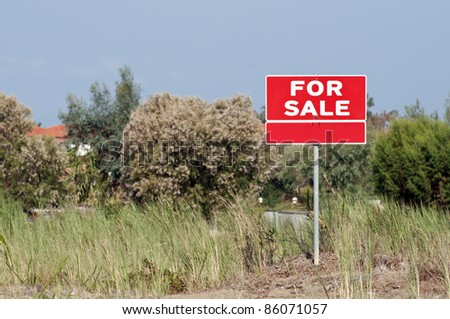Land for sale sign in empty field - stock photo