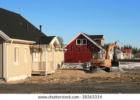 Land preparation with a small excavator around newly built homes.