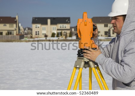 Land surveying during the winter - suburban area. - stock photo
