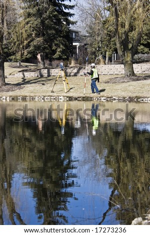 Land Surveyor and his instrument reflected in the pond. - stock photo