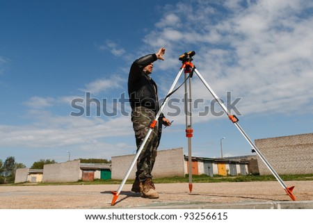 Land surveyor working with total station on a construction site. - stock photo