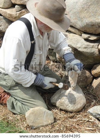 Land trust owner building a stone wall.