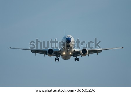 Landing aircraft with headlights on - stock photo