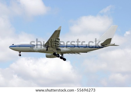 Landing airplane in the cloudy blue sky. - stock photo