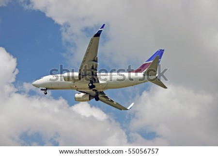 Landing airplane near the airport at blue cloudy sky background. - stock photo