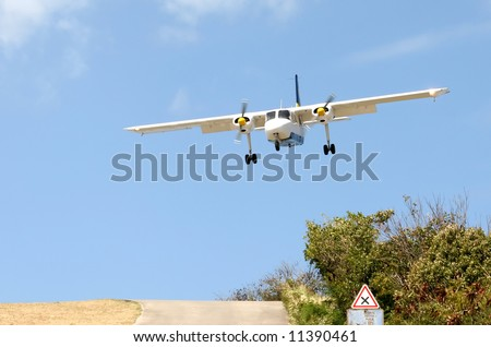 landing at St. Barth airport, Caribbean: the arrival descent is extremely steep over the hilltop traffic circle. - stock photo