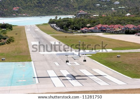 landing at St. Barth airport: the short airstrip is at the base of a steep hill ending directly on the beach. - stock photo
