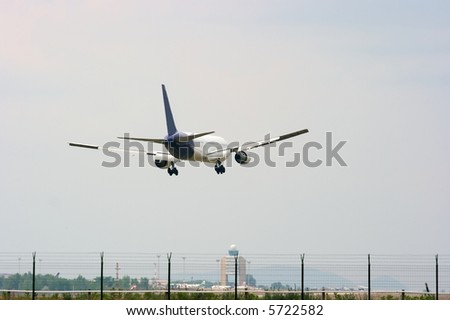 Landing commercial aircraft above the runway - stock photo
