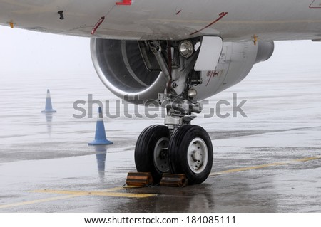 Landing gear of a plane on a rainy day - stock photo