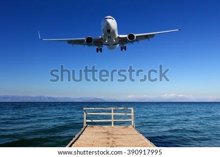 Landing in paradise - airplane approaching ground on mediterranean island - stock photo