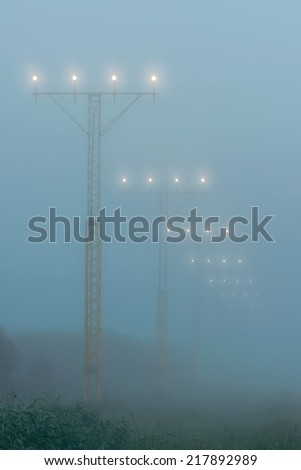 Landing lights at a airport during foggy weahter, help airplanes find the runway approach  - stock photo