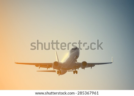 Landing of the passenger plane at sunset time.