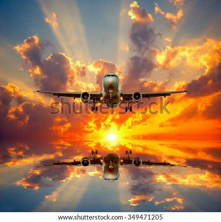 Landing of the passenger plane to the island at sunset time. - stock photo
