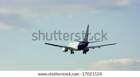 Landing passenger airplane against blue sky - stock photo