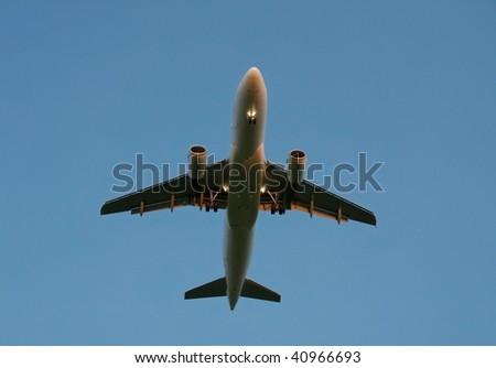 Landing plane against dusk sky - stock photo
