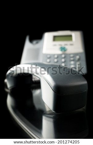 Landline telephone with receiver off the base on black desk with reflection isolated over black background. - stock photo