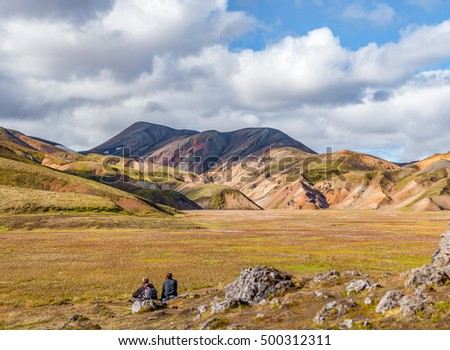 Landmannalaugar. Two hikers admiring amazing multicoloured mountains near Brennisteinsalda at the start of the Laugavegur hike in the southern highlands of Iceland, looking across a cottongrass plain