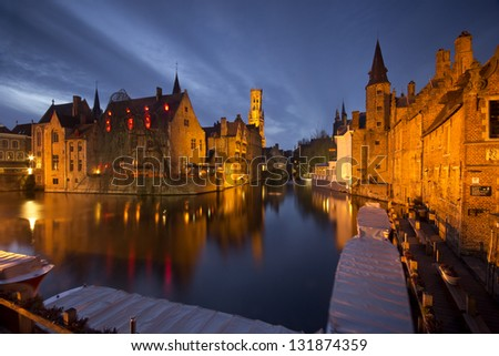 Landmarks of Bruges (Brugge) - traditional buildings near the water canal, boats and wooden jetty.