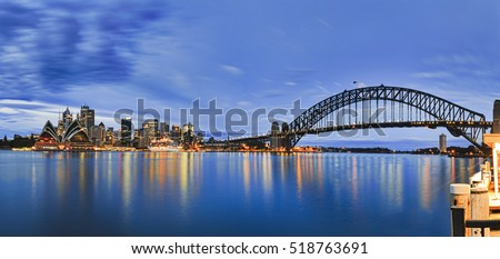 Landmarks of Sydney city CBD across Harbour with bridge, circular quay, passenger terminal and downtown skyscrapers to Kirribilli pier at blue cloudy sunrise.
