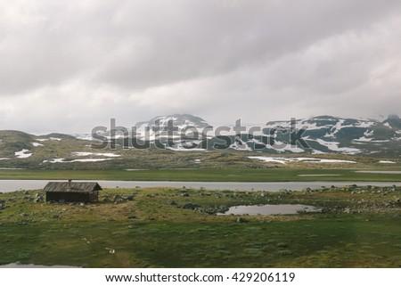 Landscape along Hardangervidda, Europe's highest mountainous plateau. Photo taken from the scenic Bergen Railway running from Oslo to Bergen (Norway). - stock photo