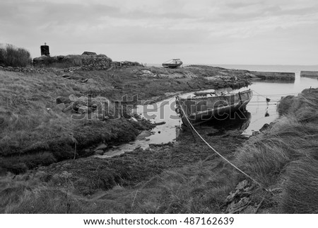 Landscape and seascape of old crofters house and old boats in Berneray in the Outer Hebrides in Scotland UK