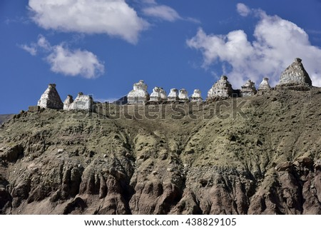 Landscape clear day with the ancient Tibetan Buddhist white stupa on the high slope and clouds in the sky near the village Basgo, Ladakh, Himalayas, Northern India. - stock photo