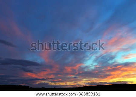 landscape colorful cirrus clouds against a blue sky at sunset - stock photo