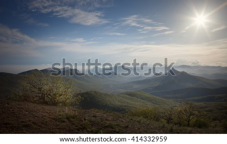 Landscape. Crimean mountains under the blue sky with clouds and sun - stock photo