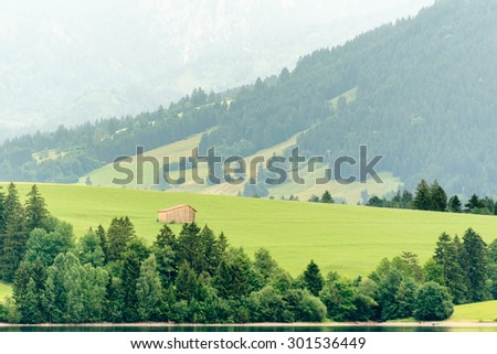 landscape from lake forggen over allgaeu meadows with wooden hut