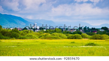 Landscape from meadow with yellow flowers and deep blue sky and village view - stock photo