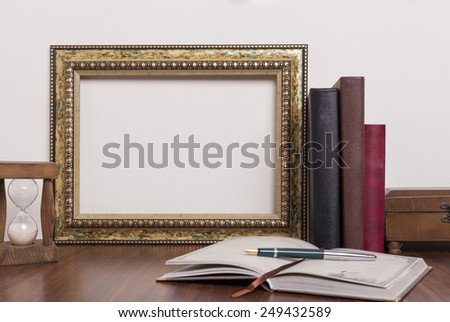 Landscape golden frame with books and hourglass on wood table - stock photo