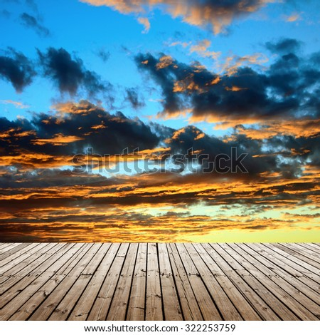 landscape golden sunset and sun beams through the cloud, view from wooden platform - stock photo