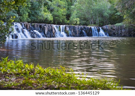 Landscape image of a small waterfall in a river. - stock photo