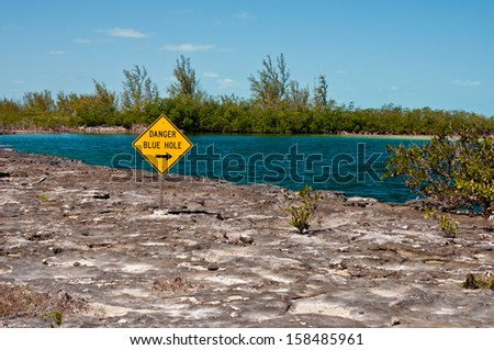 Landscape image of a yellow danger sign warning about a blue hole  in the islands of the bahamas. - stock photo