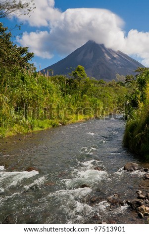 Landscape in Arenal National Park, Costa Rica, with river and volcano - stock photo