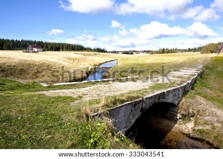 Landscape in Czech mountains Jizerske hory in the autumn with a stone bridge