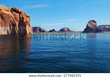 Landscape is filled with sandstone cliffs and the blue waters of Lake Powell. - stock photo
