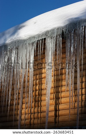 Landscape. Large icicles on the roof of a wooden house. Carpathian Mountains. Ukraine.